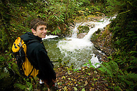 A teenager hiking along Perseverance Creek in Cumberland encounters one of the many waterfalls that follow the creek alongside the popular hiking and mountain biking trail.  Cumberland, Vancouver Island, British Columbia, Canada.