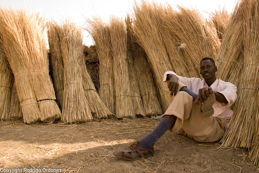A man sits in the shade, leaning against the materials he is displaying for sale, at the grass market, in Abyei.