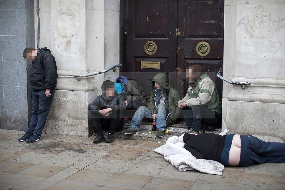 © Licensed to London News Pictures . 06/04/2017 . Manchester , UK . A group of men huddle in a doorway on Piccadilly Gardens , one lies in an unresponsive state on the pavement , another stands slouched back against the wall . An epidemic of abuse of the drug spice by some of Manchester's homeless population , in plain sight , is causing users to experience psychosis and a zombie-like state and is daily being witnessed in the Piccadilly Gardens area of Manchester , drawing large resource from paramedic services in the city centre . Photo credit : Joel Goodman/LNP