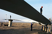 Gansu, China - 26 Feb 2010. Maintenance workers fix the blades of a windmill at Guazhou wind farm near Yumen, Gansu province, China. China has set a target for renewable energy consumption of 40 percent of the market by the year 2050.