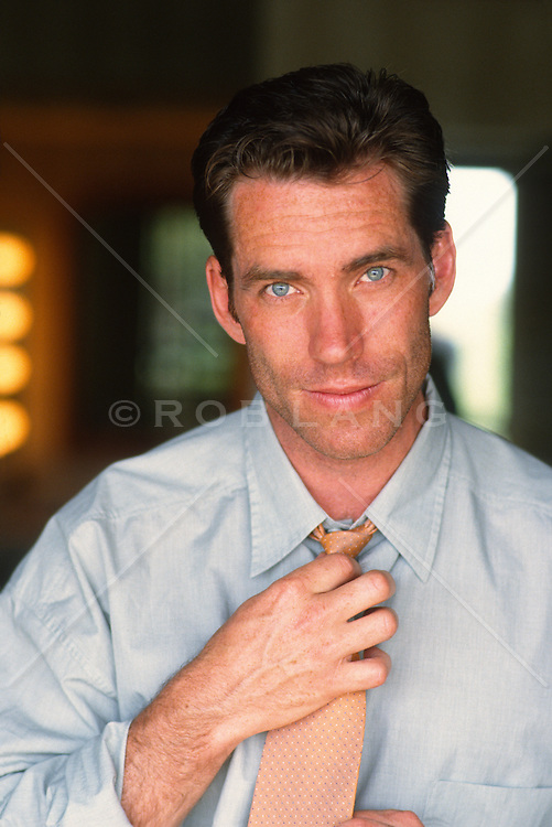 Blue eyed man putting on his tie looking at camera