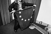 """ROME, ITALY - 24 JANUARY 2013: A man folds a EU flag after a press conference given by members of the center-left coalition Pierluigi Bersani (PD - Democratic Party, leader running for Prime Minister), Bruno Tabacci (Democratic Center) and Nichi Vendola (Left Ecology Freedom) at the Ripetta Residence in Rome, on January 24, 2013. Pierluigi Bersani, running for Prime Minister in the 2013 elections in Italy, said he wouldn't dump his ally Nichi Vendola for former PM Mario Monti.  A general election to determine the 630 members of the Chamber of Deputies and the 315 elective members of the Senate, the two houses of the Italian parliament, will take place on 24–25 February 2013. The main candidates running for Prime Minister are Pierluigi Bersani (leader of the centre-left coalition """"Italy. Common Good""""), former PM Mario Monti (leader of the centrist coalition """"With Monti for Italy"""") and former PM Silvio Berlusconi (leader of the centre-right coalition). ### ROMA, ITALIA - 24 GENNAIO 2013: un uomo rotola una bandiera dell'Unione Europea dopo una conferenza stampa presieduta dai membri della coalizione di centro-sinistra Pierluigi Bersani (PD - Partito Democratico, leader candidate alla Presidenza del Consiglio), Bruno Tabacci (Centro Democratico) e Nichi Vendola (Sinistra Ecologia Libertà) al Residence Ripetta a Roma, il 24 gennaio 2013. Le elezioni politiche italiane del 2013 per il rinnovo dei due rami del Parlamento italiano – la Camera dei deputati e il Senato della Repubblica – si terranno domenica 24 e lunedì 25 febbraio 2013 a seguito dello scioglimento anticipato delle Camere avvenuto il 22 dicembre 2012, quattro mesi prima della conclusione naturale della XVI Legislatura. I principali candidate per la Presidenza del Consiglio soon Pierluigi Bersani (leader della coalizione di centro-sinistra """"Italia. Bene Comune""""), il premier uscente Mario Monti (leader della coalizione di centro """"Con Monti per l'Italia"""") e l'ex-premier Silvio Berlusconi (leader della c"""