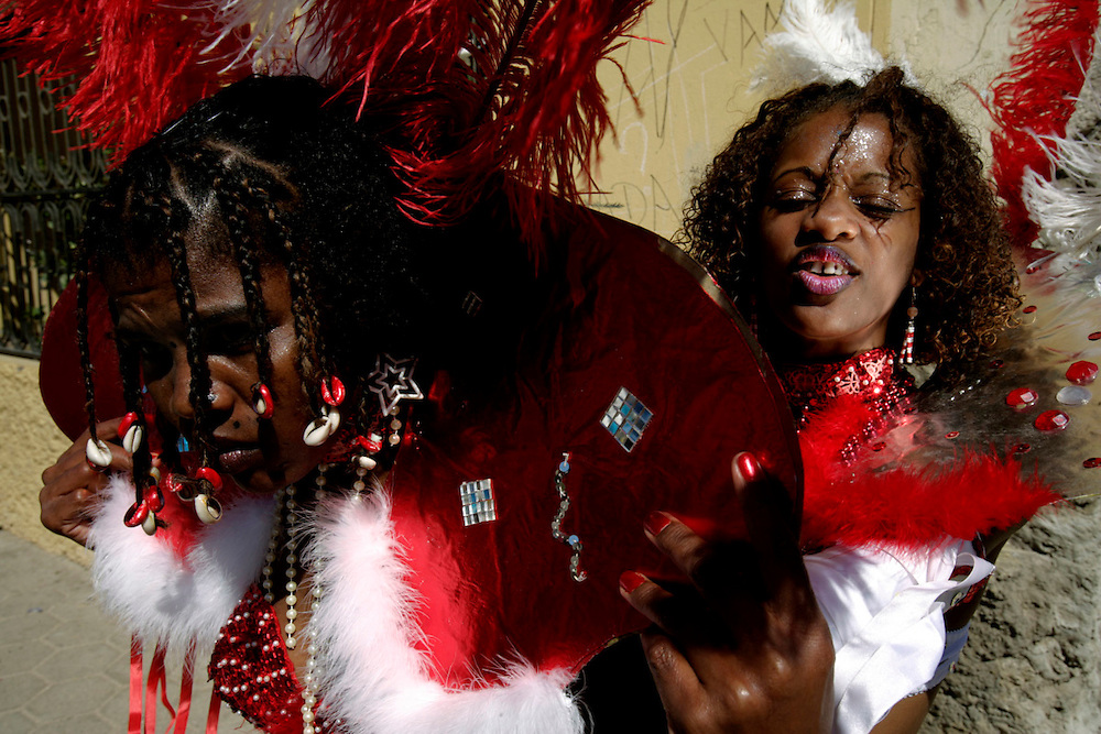 Two girls preparing their costumes before parading in Mindelos Tuesday Carnival March.