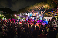 """ROME, ITALY - 27 JUNE 2017: The audience watches the premiere of the """"Don Giovanni OperaCamion"""", an open-air opera performed on a truck in San Basilio, a suburb in Rome, Italy, on June 27th 2017.<br /> <br /> Director Fabio Cherstich's idae of an """"opera truck"""" was conceived as a way of bringing the musical theatre to a new, mixed, non elitist public, and have it perceived as a moment of cultural sharing, intelligent entertainment and no longer as an inaccessible and costly event. The truck becomes a stage that goes from square to square with its orchestra and its company of singers in Rome. <br /> <br /> """"Don Giovanni Opera Camion"""", after """"Don Giovanni"""" by Wolfgang Amadeus Mozart is a new production by the Teatro dell'Opera di Roma, conceived and directed by Fabio Cherstich. Set, videos and costumes by Gianluigi Toccafondo. The Youth Orchestra of the Teatro dell'Opera di Roma is conducted by Carlo Donadio."""