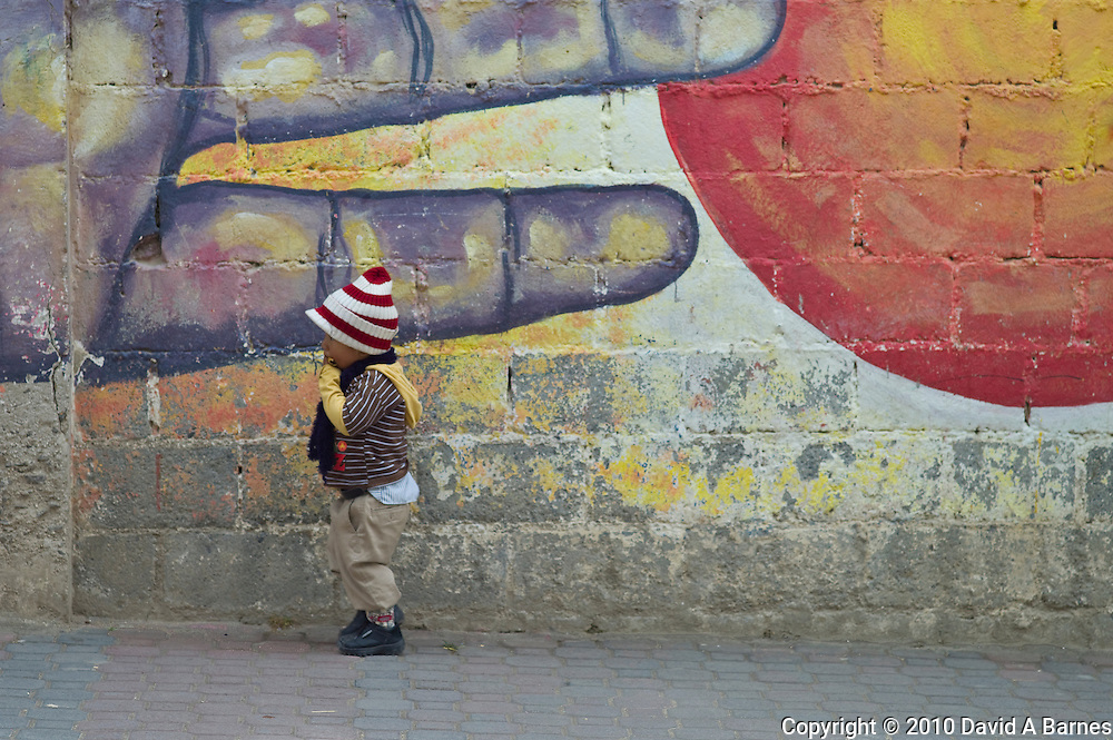 Little boy standing by painted wall with graffiti, Saraguro, Ecuadore