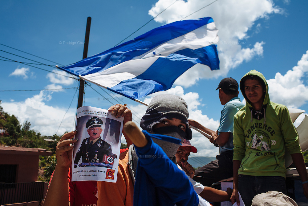 Supporters of ousted Honduran President Manuel Zelaya shows a picture of interim leader Roberto Micheletti caricaturized as Germany's Nazi dictator Adolf Hitler, during a rally to protest against the military coup on July 8, 2009.