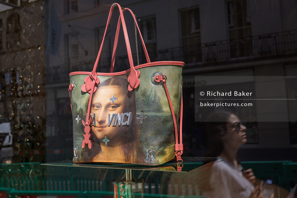 A luxury shop window of Louis Vuitton featuring their exclusive range of bags with the face of Leonardo da Vinci's Mona Lisa - a collaboration with the artist Jeff Koons and part of work entitled The Masters Collection, on 5th July 2017, on New Bond Street, in London England.