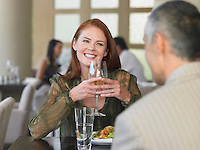 Woman smiling at man over meal in restaurant