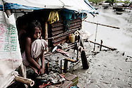 """Bangladesh, Gabruia sep. 2009. Denne familie har bygget deres egen ø, efter at cyklonen """"Aila"""" i maj 2009 ødelagde 2 mio. menneskers hjem og digerne brød sammen, som ellers beskyttede deres huse, marker og drikkevand. 30.000 menneskers drikkevand er nu blandet med saltvand, men der er ikke andet i området. Klimaforandringer og naturkatastrofer"""
