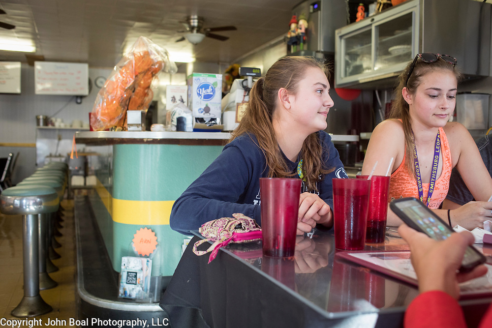 Haley Mapes, 17, left and Hannah Yoder, 17, sit at a table with fellow members of the Smithsburg High School Marching Band inside the Dixie Diner, in downtown Smithsburg, Maryland, on Tuesday, September 26, 2017. Smithsburg is a very different town than the southern part of the district that includes Potomac and Germantown. Originally a District that was mostly rural, but included towns like Frederick and Hagerstown, Maryland's 6th District was redistricted in 2011, combining rural northern Maryland regions with more affluent communities like near Washington D.C. turning the district from Republican to Democrat. <br />  <br /> CREDIT: John Boal for The Wall Street Journal<br /> GERRYMANDER