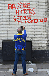 An Arsenal fan takes pictures of graffiti saying 'Arsene haters get out of our club'