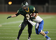 Kennedy's Trevor Heitland (33) is pulled down by Wahlert's Nate Pierotti (7) after a catch during the first half of the game between Cedar Rapids Kennedy and Dubuque Wahlert at Kingston Stadium in Cedar Rapids on Friday night, October 21, 2011.