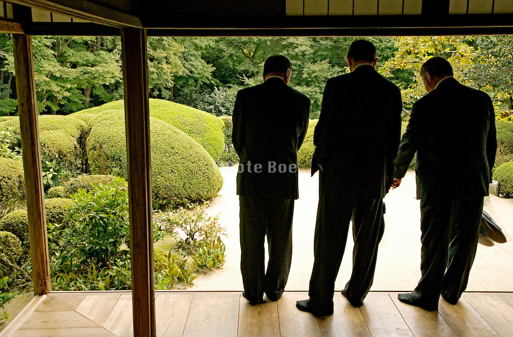 western businessmen at a traditional Japanese Zen garden and tea house
