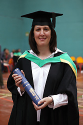 Portrait of woman in graduation gown holding certificate,