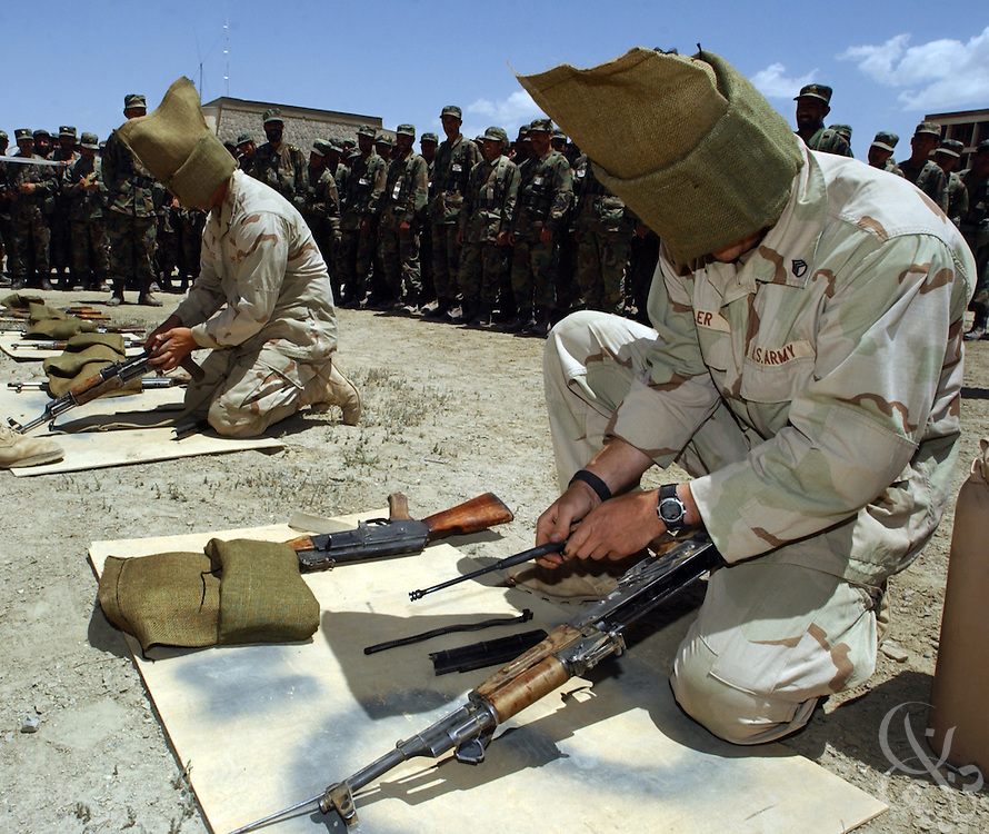 U.S. Army Green Berets from the 3rd Special Forces Group from Fort Bragg, NC wear hoods as they demonstrate to Afghan soldiers how to disassemble an AK-47 assault weapon during a training competition May 27, 2002 at an Afghan National Army (ANA) training facility in Kabul, Afghanistan. U.S. Special Forces conduct  ten week training courses for the Afghan Army in the hope that a better trained military will mean a more stable Afghanistan.
