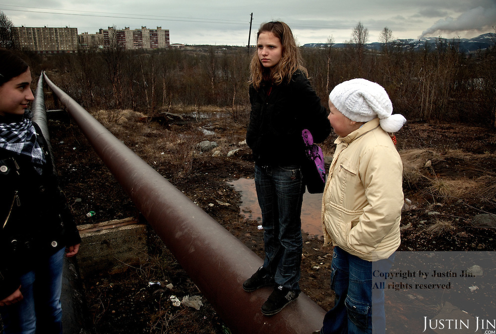 Girls stand on hot-water pipes in Zapolyarny, a town built for its nickel mining combine. Sulphur dioxide emitted from the factory (in the background on the right)kills vegetation, pollutes ground water and causes asthma, especially among children.