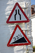 Red triangular signs for narrow steep road, St Mawes, Cornwall, England
