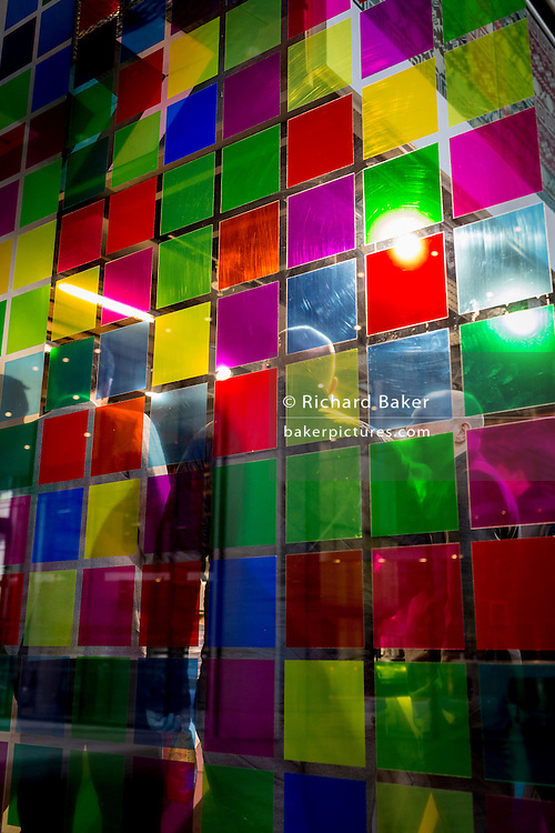 A theme of repeating coloured squares and the backs of queueing lunchtime customers, on 16th February 2017, in the City of London, England.