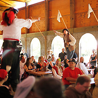Members of Drunk 'N Sailor Bob Walters, left, portraying Capt. Amos Muirhead, and Dieter Zimmerman, portraying Phillip McGuinness, sing along with the crowd during lunch at the Highland Renaissance Festival in Eminence, Ky., on 6/19/10. Photo by David Stephenson
