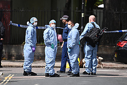 © Licensed to London News Pictures. 12/07/2020. London, UK. Police forensics and sniffer dogs at The scene of a murder on the Black Prince Estate in Kennington South London in which a man, believed to be in his 30s, was stabbed to death late last night . Photo credit: Ben Cawthra/LNP
