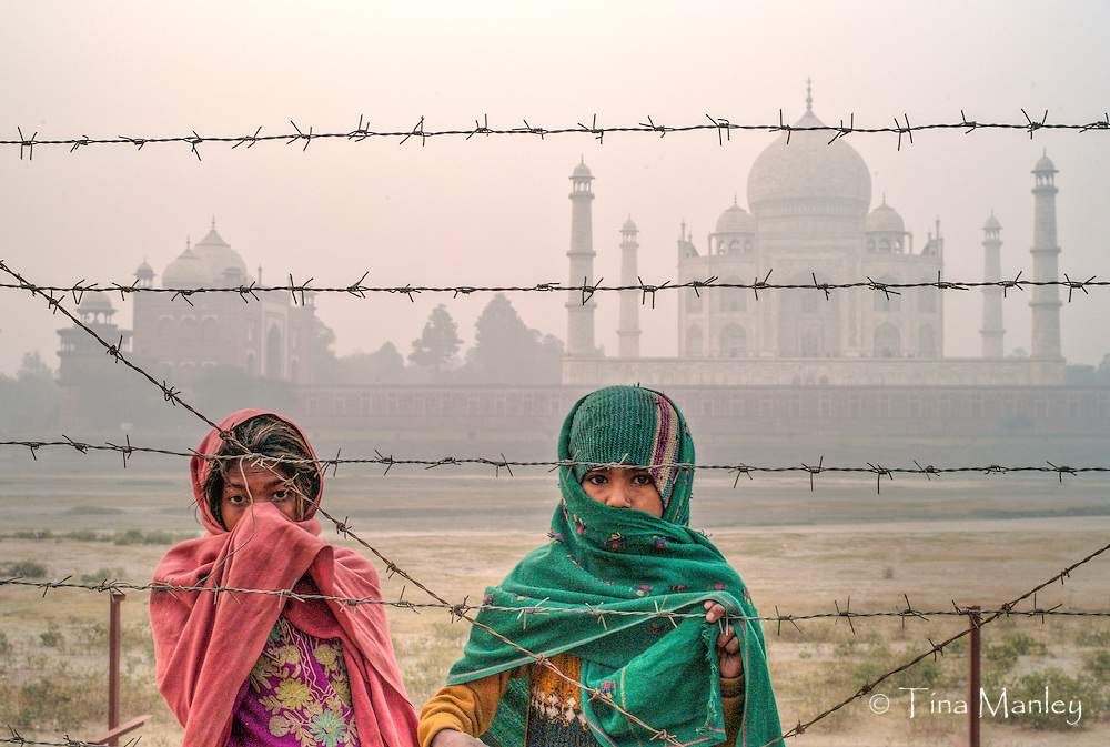 Young girls begging at dawn behind barbed wire behind the Taj Mahal, in Agra, India