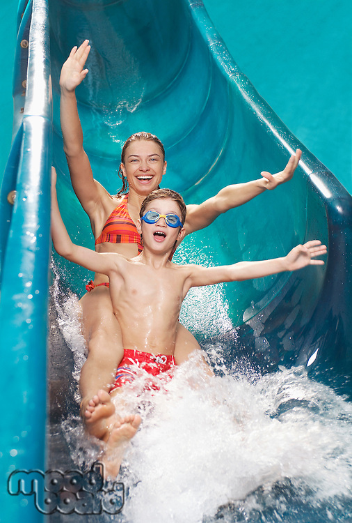 Brother and sister (7-12) with arms outstretched on water slide