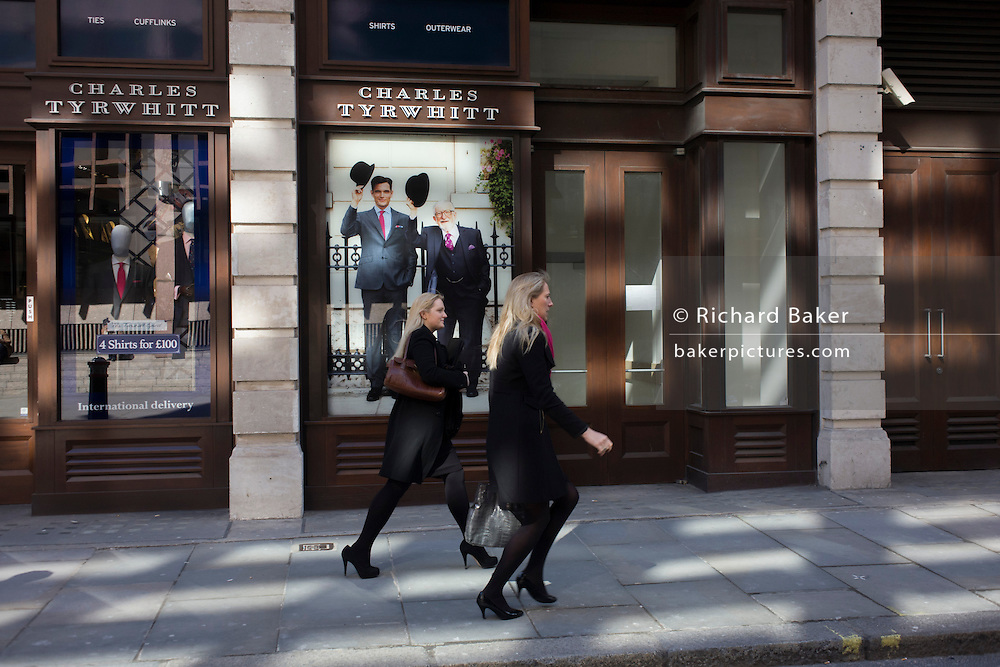 Two women on their way to a waiting taxi run past the Charles Tyrwhitt menswear outfitters at Liverpool Street in the City of London, the capital's heart of its financial district - a good location for suits and businesswear. A pair of Englishmen raise their bowler hats in a gesture from a previous era, when hats said much of your social standing, a summary of your position in the class system. In the 21st century though, the hat is largely an item of clothing to wear only for extreme cold or heat. A leggy girl strides past the shop frontage, seemingly curious of this bygone gentlemanly tradition.
