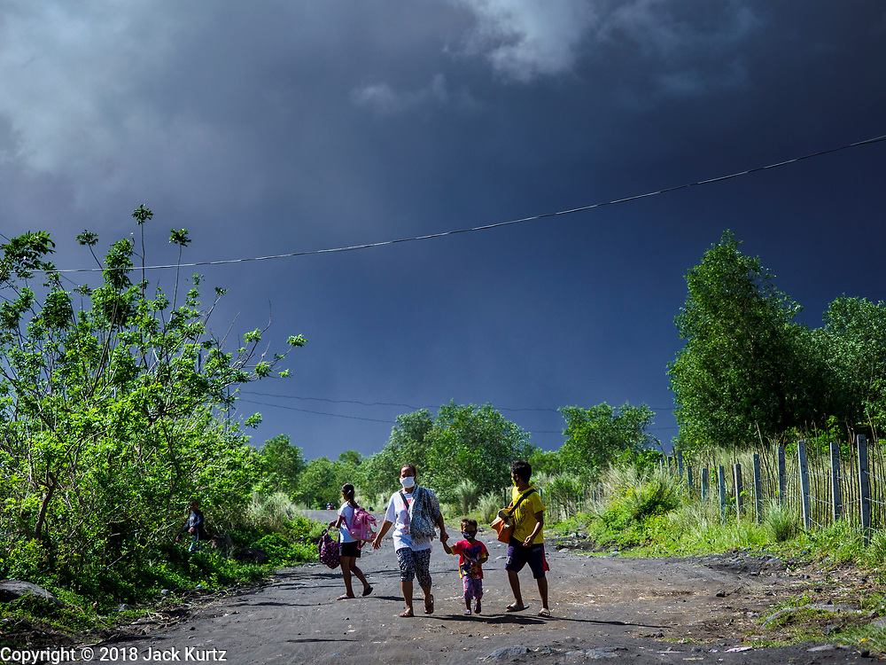 "22 JANUARY 2018 - CAMALIG, ALBAY, PHILIPPINES: People who live on the slopes of Mayon volcano rush out of the area after the a large eruption in the volcano Monday. There were a series of eruptions on the Mayon volcano near Legazpi Monday. The eruptions started Sunday night and continued through the day. At about midday the volcano sent a plume of ash and smoke towering over Camalig, the largest municipality near the volcano. The Philippine Institute of Volcanology and Seismology (PHIVOLCS) extended the six kilometer danger zone to eight kilometers and raised the alert level from three to four. This is the first time the alert level has been at four since 2009. A level four alert means a ""Hazardous Eruption is Imminent"" and there is ""intense unrest"" in the volcano. The Mayon volcano is the most active volcano in the Philippines. Sunday and Monday's eruptions caused ash falls in several communities but there were no known injuries.    PHOTO BY JACK KURTZ"