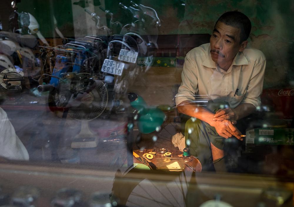 HANOI, VIETNAM - CIRCA SEPTEMBER 2014:  Portrait of Vietnamese man through the window of his shop in the traditional Old Quarter in Hanoi, Vietnam.