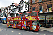 A York City open top red sightseeing tour bus travels along Pavement.
