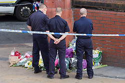 © Licensed to London News Pictures . 14/07/2013 . Manchester , UK . A group of Fighters lay flowers and watch over tributes left at the scene where a fire fighter, identified as Stephen Hunt, died while tackling a fire in a store-room of Paul's Hair World in Oldham Street, Manchester. Two 15-year-old girls arrested on suspicion of manslaughter. Photo credit : Joel Goodman/LNP