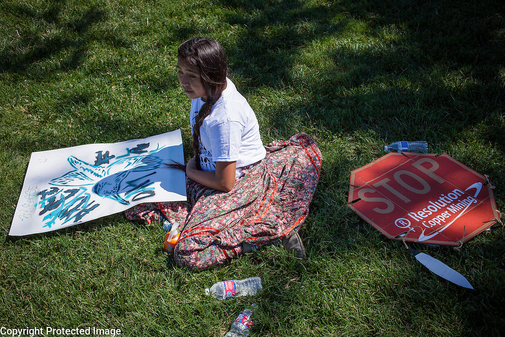 "Base Pike, 10, Apache, sits on the U.S. Capitol lawn prior to a demonstration led by members of the San Carlos Apache Tribe and their supporters to protest the transfer of Apache land to a private mining corporation.  In December 2014, a rider to the National Defense Authorization Act handed over Oak Flat to a private Australian-British owned company looking to mine copper.  The Apache are currently ""occupying"" Oak Flat, and travelled to D.C. to protest the action.  In response, Rep. Raul Grijalva (D-AZ-3), proposed the Save Oak Flat Act (H.R. 2811) in June, 2015 to repeal the land exchange.  John Boal Photography"
