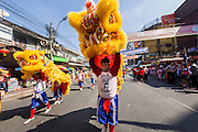 31 JANUARY 2014 - BANGKOK, THAILAND:   A Chinese Lion dancer walks down a street during Lunar New Year festivities, also know as Tet and Chinese New Year, in Bangkok. This year is the Year of the Horse. The Lion Dance scares away evil spirits and brings prosperity and luck. Ethnic Chinese make up about 14% of Thailand and Chinese holidays are widely celebrated in Thailand.     PHOTO BY JACK KURTZ