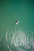 Vertical aerial viw of speed boat anchored on calm clear sea