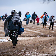 In subfreezing snowy weather, refugees walk the unoffical refugee crossing from the Tabanovce, Macedonia Train Station across the Serbian border.  A daily average of 2,200 refugees have crossed into Serbia throughout the winter.  Warmer months saw highs of 10,000 arrivals. Limited to what belongings they can carry with them, many have gone without food and water for extended periods. They have escaped their own country in conflict, taken a perilous boat ride from Turkey to Greece, and then moved onward through disorienting foreign lands in search of a peaceful home. Most refugees are headed to welcoming Germany. They are from  Afghanistan, Iraq, and Syria, with a wide range of socioeconomic backgrounds.