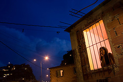 Ivonne Baloid, a community activist, sits in her window in the evening in Coche, a poor Caracas hillside slum
