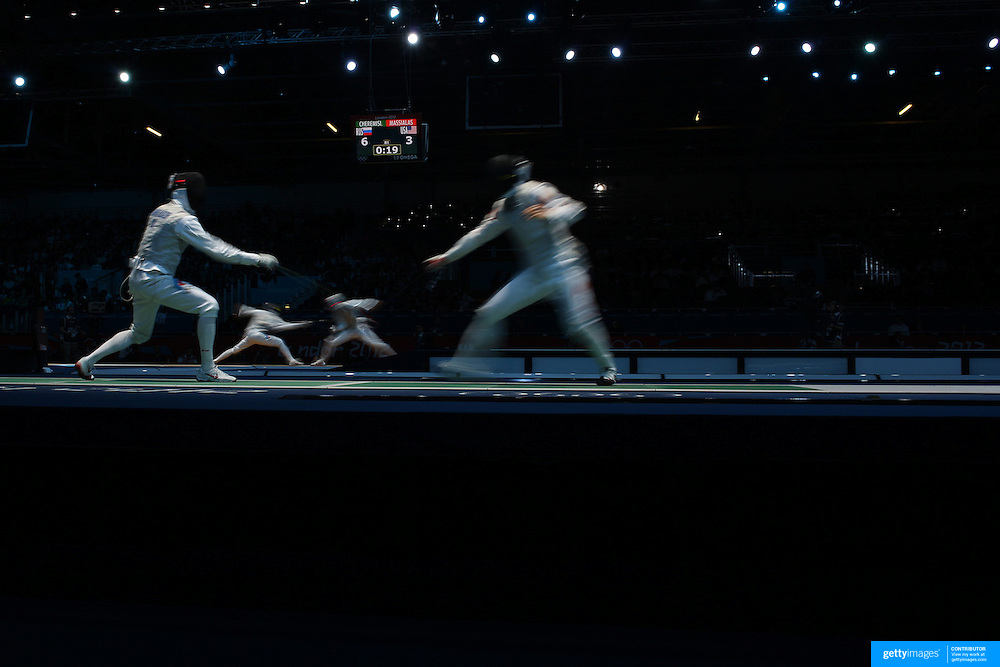 A blur of motion as Artur Akhmatkhuzin, Russia, (left) competes with Jianfei Ma, China, (foreground) and Alexey Cheremisinov, Russia, competes with Alexander Massialas, USA, (background) in the Men's Foil Individual event during the Fencing competition at ExCel South Hall during the London 2012 Olympic games. London, UK. 31st July 2012. Photo Tim Clayton