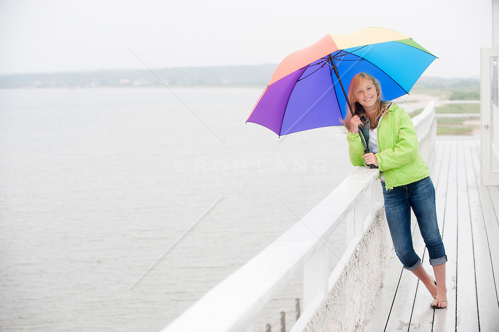 teenage girl holding a rainbow umbrella while standing on a deck overlooking the bay in East Hampton,NY