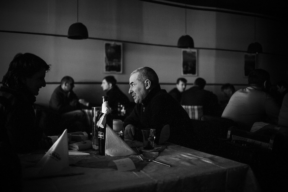 Customers continue with their meal during one of the regular rolling power outages that go through the city, Pristina