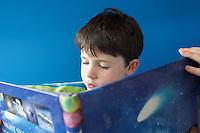 Boy (5-6) reading book indoors close-up