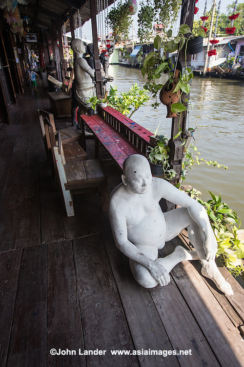 Artist's House or in Thai Baan Silapin - Long ago, these types of old Thai teak houses were very typical along the klongs but today are becoming rare, usually replaced by concrete buildings. Baan Silapin has been beautifully restored, with unusual features such as human statues sitting by the water, gazing at life passing by.  Artist House is owned by Chumpol Akkapantanon - the house was run down when it was bought before being restored to its present glory.  It's a great escape from the crazy traffic of Bangkok - it has beauty in its rustic sort of way with its own 600 year old chedi in the back yard.  There is a coffee shop inside and tradtional puppet shows are performed every afternoon, using puppets from the famous Joe Louis theatre that was once held at the Suan Luan Bazaar.