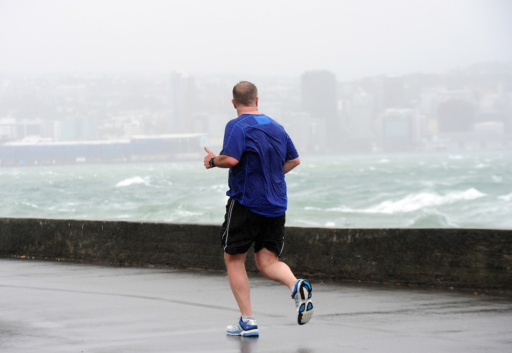 A runner takes on the weather on Oriental Parade as high winds lash the capital, Wellington, New Zealand, Monday, October 14, 2013. Credit:SNPA / Ross Setford