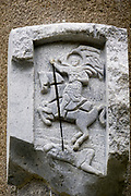 A basrelief of a knight on horseback impaling a ground soldier