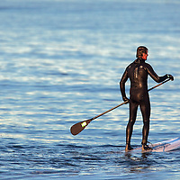 Stand up paddle surfing , or in the Hawaiian language Hoe he'e nalu, is an emerging global sport with a Hawaiian heritage. It can be traced back to the early days of Polynesia. The sport is an ancient form of surfing, and began as a way for surfing instructors to manage their large groups of learner surfers, as standing on the board gave them a higher viewpoint, increasing visibility of what was going on around them - such as incoming swell.  Here a rider patrols and surfs waves from Sandy Hook National Park in Monmouth County New Jersey