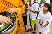 """23 APRIL 2013 - BANGKOK, THAILAND:  A Thai girl watches a monk collects books for literacy projects during the opening ceremony to mark Bangkok as the World Book Capital City 2013. UNESCO awarded Bangkok the title. Bangkok is the 13th city to assume the title of """"World Book Capital"""", taking over from Yerevan, Armenia. Bangkok Governor Suhumbhand Paribatra announced plans that the Bangkok Metropolitan Administration (BMA) intends to encourage reading among Thais. The BMA runs 37 public libraries in the city and has modernised 14 of them. It plans to build 10 more public libraries every year. Port Harcourt, Nigeria will be the next World Book Capital in 2014. .PHOTO BY JACK KURTZ"""