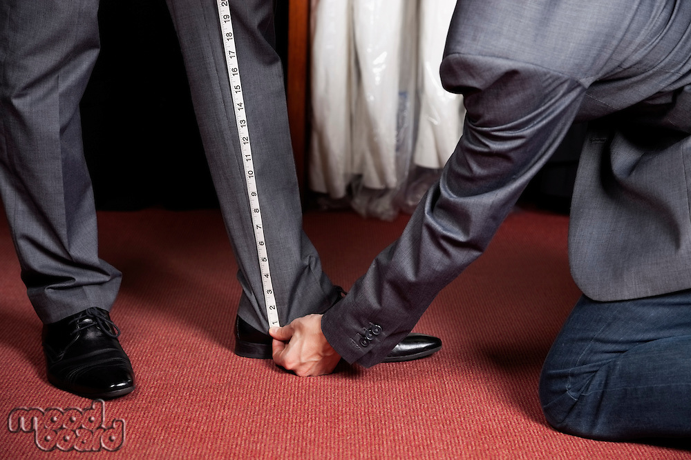 Cropped image of tailor measuring man's trouser in store