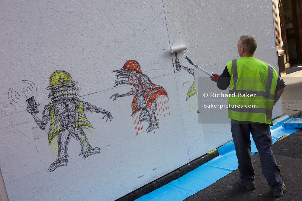 Contractor in high-vis vest paints over construction hoarding of similar cartoon characters by street artist Nathan Bowen.