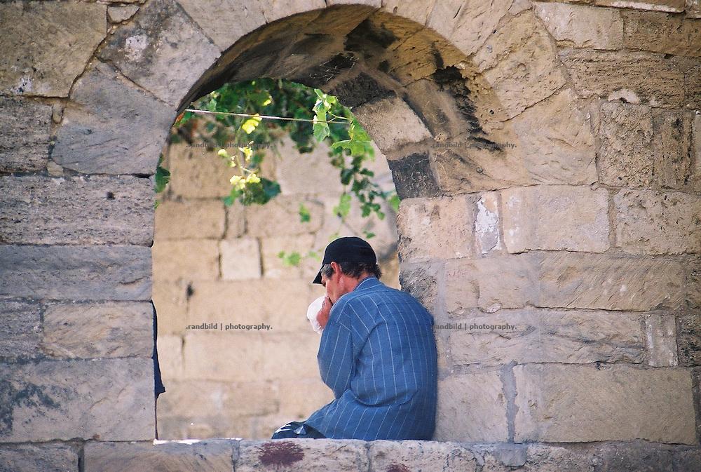 Ein Drogenabhängiger schnüffelt Klebstoff in einem alten Gemäuer der Altstadt Ischeri Scheher der aserbaidschanischen Hauptstadt Baku. A drug addicted sniffs a bag of glue in Baku, aserbaijan.