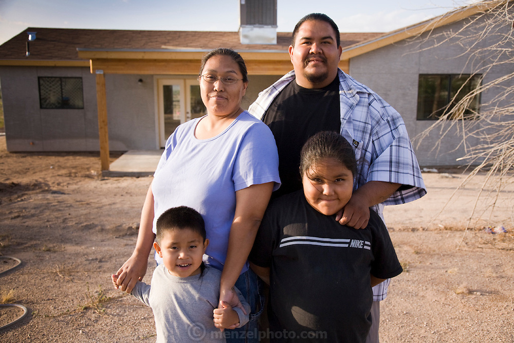 Assistant carpenter and tattooist Louie Soto with his family at his new home in Sacaton, Arizona. (Louie Soto is featured in the book What I Eat: Around the World in 80 Diets.) Soto built a new home, financed by casino profits and built by the Gila River Indian Community.