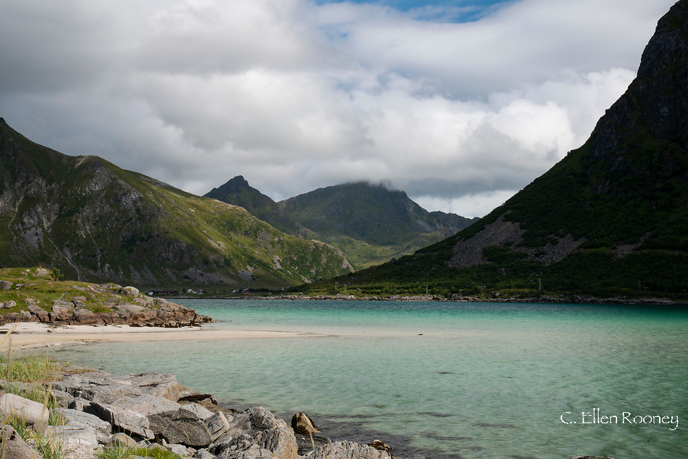 Aqua coloured water in Flakstadpollen, a sea bay surrounded by mountains, Flakstadoy, Lofoten Islands, Norway